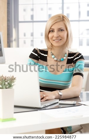 Portrait of casual blonde caucasian secretary working with laptop computer in brightly lit office, smiling at camera. - stock photo