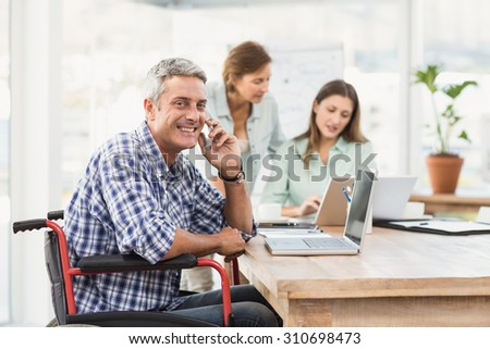 Portrait of casual businessman in wheelchair phoning in the office - stock photo