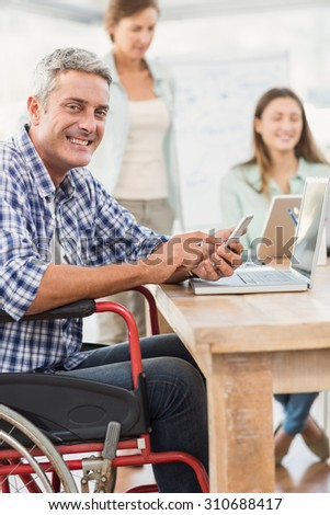 Portrait of casual businessman in wheelchair with smartphone in the office - stock photo