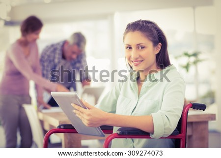 Portrait of casual businesswoman in wheelchair using tablet in the office - stock photo