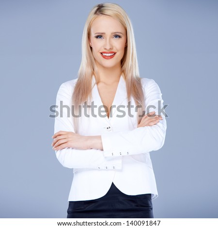 Portrait of casual dressed blond woman posing with arms crossed over natural background - stock photo