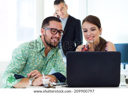 Portrait of casual executives working together at a meeting with laptop. - stock photo