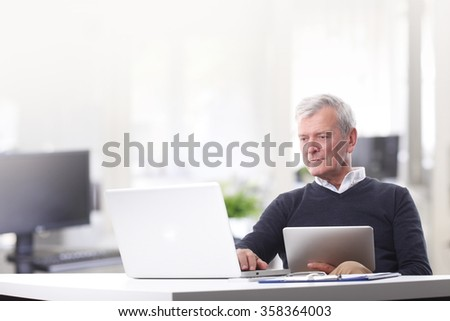 Portrait of casual professional man sitting at office in front of laptop and touching keyboard while holding in his other hand a digital tablet.  - stock photo