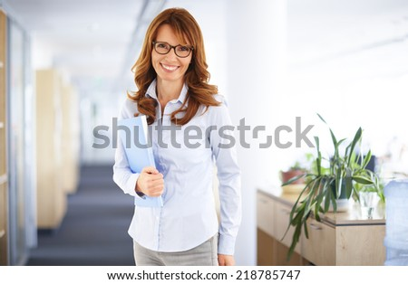 Portrait of casual sales woman holding file, while standing at office.  - stock photo