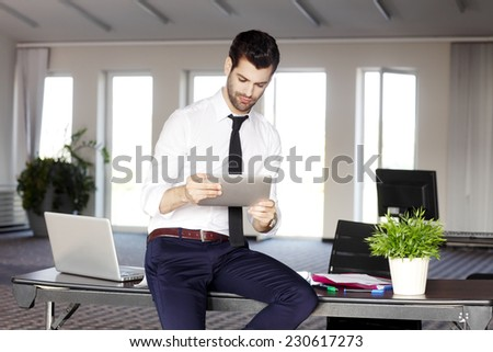 Portrait of casual young broker sitting at desk while using digital tablet. Business people.  - stock photo