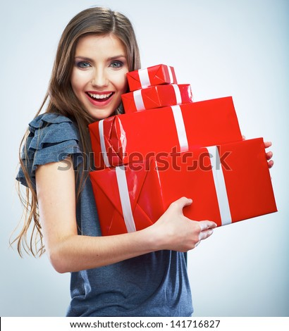 Portrait of casual young happy smiling woman hold red gift box. Isolated studio background female model. - stock photo