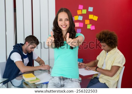 Portrait of casual young woman gesturing thumbs up - stock photo