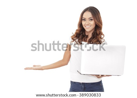 portrait of casual young woman presenting copy space while holding a laptop isolated on white background - stock photo