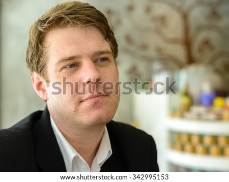 Portrait of Caucasian businessman sitting in coffee shop - stock photo