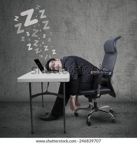 Portrait of caucasian businessman sleeping at desk with laptop computer - stock photo