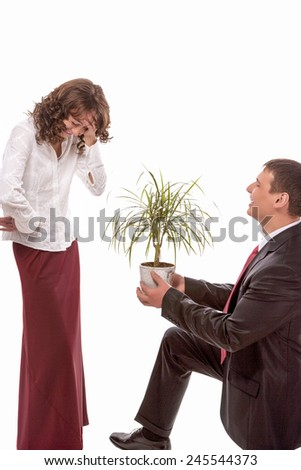 Portrait of Caucasian Couple Together Having Fun. Allegoric Flower Gift Presentation to Female. Isolated Over White. Vertical Image Composition - stock photo