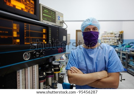 Portrait of caucasian doctor looking at camera in hospital surgery room with professional equipment and instruments - stock photo