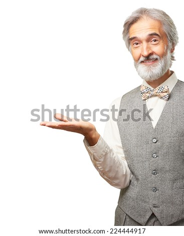 Portrait of caucasian handsome smiling aged man with a gray beard and bowtie pointing with a hand isolated on white background - stock photo