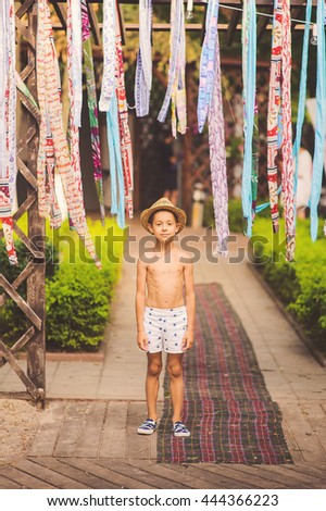 Portrait of caucasian happy baby (boy) in the hat. Child is smiling in summer day at the beach. Kid is enjoying ocean. Boy at the beach wearing a sun hat grinning happily at the camera.  - stock photo
