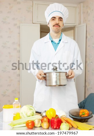 Portrait of caucasian male cook with pan and vegetables at kitchen - stock photo