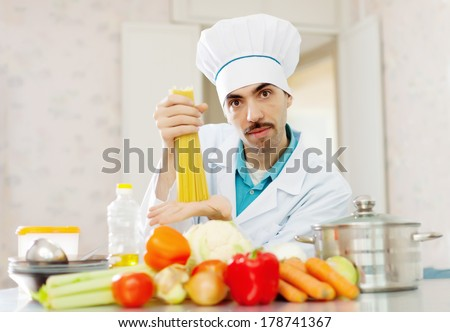 Portrait of caucasian male cook with spaghetti and vegetables at kitchen - stock photo