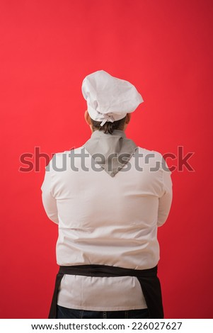 Portrait of caucasian man with chef uniform thinking. View from behind - stock photo