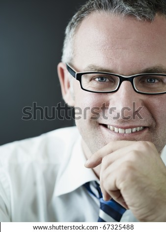 portrait of caucasian mature business man with hand on chin, looking at camera. Vertical shape, head and shoulders, front view, copy space - stock photo