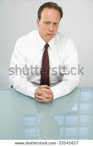 Portrait of Caucasian middle aged businessman sitting at desk. - stock photo