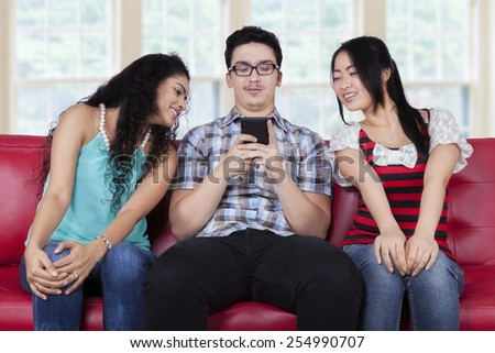 Portrait of caucasian person sitting on sofa with curios girls looking at his smart phone - stock photo