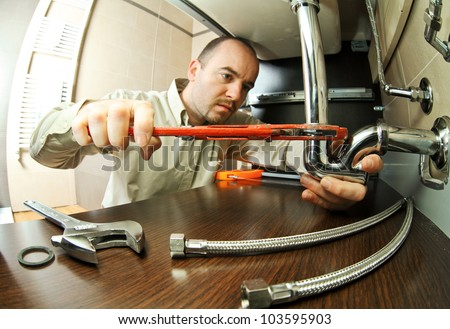 portrait of caucasian plumber at work - stock photo