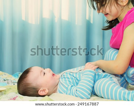 Portrait of caucasian sister and brother children playing at home  - stock photo