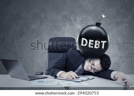 Portrait of caucasian worker sleeping on desk with laptop and a bomb of debt. Concept of financial crisis - stock photo