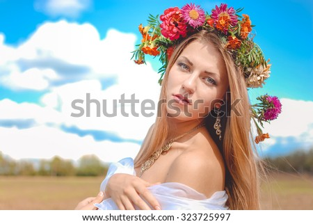 Portrait of charming beautiful girl in aster wreath looking at camera. Young woman with naked shoulder on blurred summer outdoor background. - stock photo