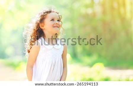 Portrait of charming curly little girl enjoying summer sunny day, nature background - stock photo