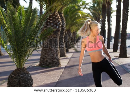Portrait of charming female jogger stretching leg muscle while standing in palm park on running road, fit caucasian woman with beautiful figure do physical exercises outdoors, copy space area for text - stock photo