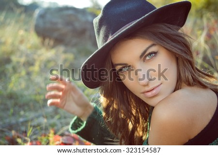 Portrait of charming girl in black hat and green sweater. Young woman with naked shoulder looking at camera on fall blurred countryside - stock photo