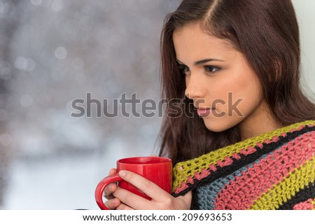 Portrait of charming girl in sweater holding cup. young woman sitting by window with cup of tea. - stock photo