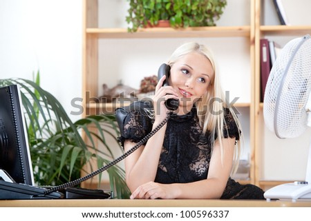portrait of charming girl talking on the phone at work - stock photo