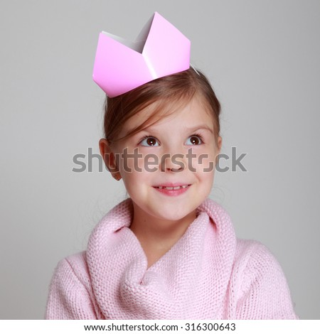 Portrait of charming smiling child in a pink knitted dress with a pink crown on her head holding a small gift on Holiday - stock photo