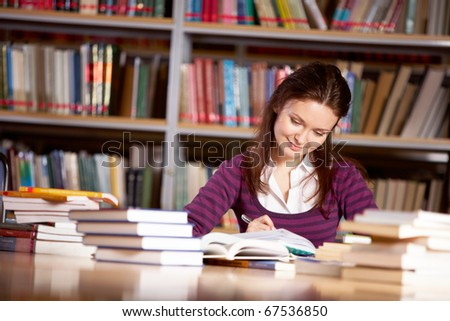 Portrait of charming student getting ready for report in college library - stock photo