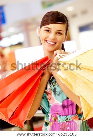 Portrait of charming woman with paper bags looking at camera in the mall - stock photo