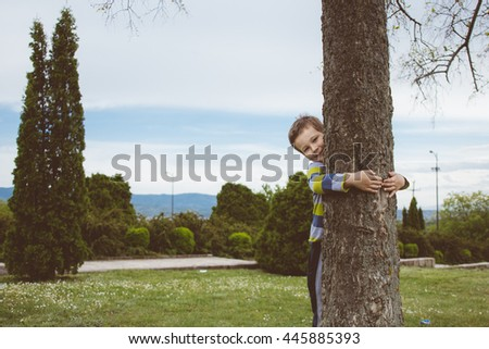 Portrait of charming young boy, affectionately embracing a tree, on leisure time, outdoors - stock photo