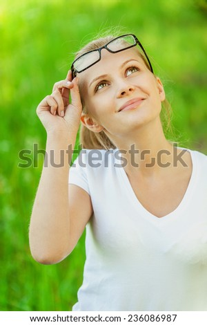 Portrait of charming young smiling woman in glasses on green background of city park. - stock photo
