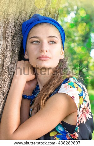 portrait of charming, young woman holding her hand beside her cheeks background summer green park.  - stock photo