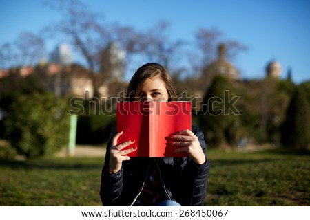 Portrait of charming young woman with red book held up close to her face, cute female covering half face with a book while sitting in the park at sunny afternoon - stock photo