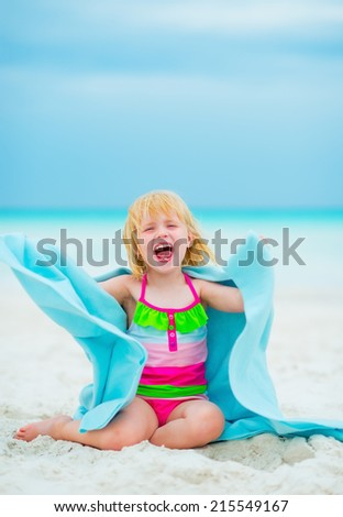 Portrait of cheerful baby girl in towel sitting on beach - stock photo