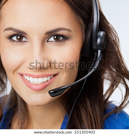 Portrait of cheerful beautiful young support phone operator in headset - stock photo