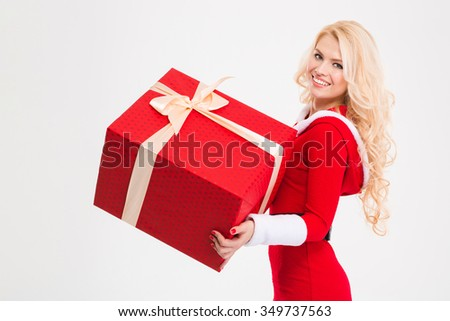 Portrait of cheerful blonde young female in santa claus clothes holding big red present over white background - stock photo