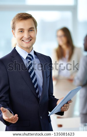 Portrait of cheerful boss with touchpad looking at camera - stock photo