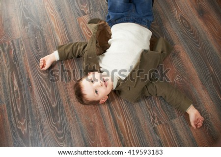 Portrait of cheerful boy lying on wood background and smiling - stock photo
