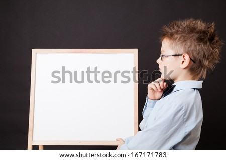 Portrait of cheerful boy pointing on white banner on the black background - stock photo