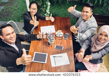 portrait of cheerful business group giving thumbs up while having a break at cafe - stock photo