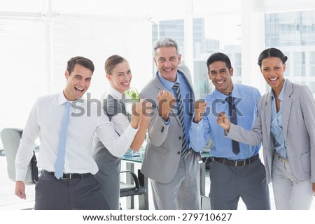 Portrait of cheerful business people cheering in the office - stock photo