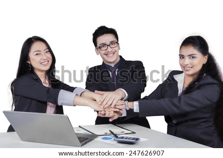 Portrait of cheerful business people smiling at the camera while joining their hands - stock photo