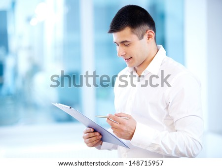Portrait of cheerful businessman reading his notes - stock photo